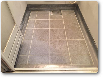 白い汚れでまだらになった浴室床